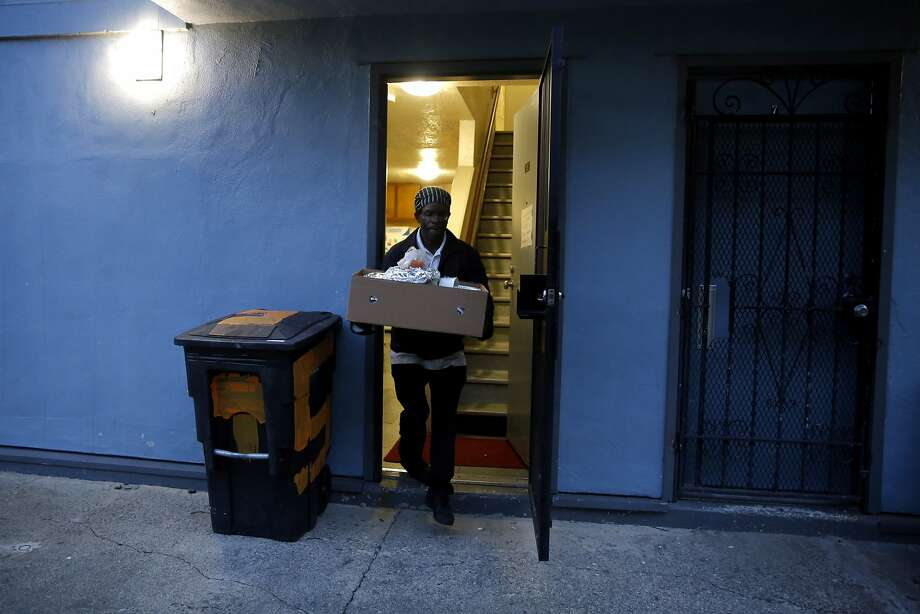 Kevin Clark carries a box of food out of the unit where they prepared it at a housing complex in the Potrero Hill neighborhood of San Francisco, California, on Wednesday, Dec. 16, 2015. Photo: Connor Radnovich, The Chronicle