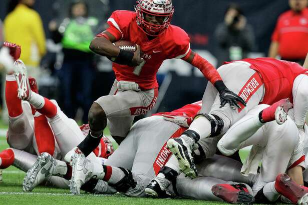 Bremond Tigers quarterback Roshauud Paul runs through a pile of players during the 2A Division II football state championships at NRG Stadium Thursday, Dec. 17, 2015, in Houston. Bremond beat Albany 35-20 to win the championship for the second year in a row.