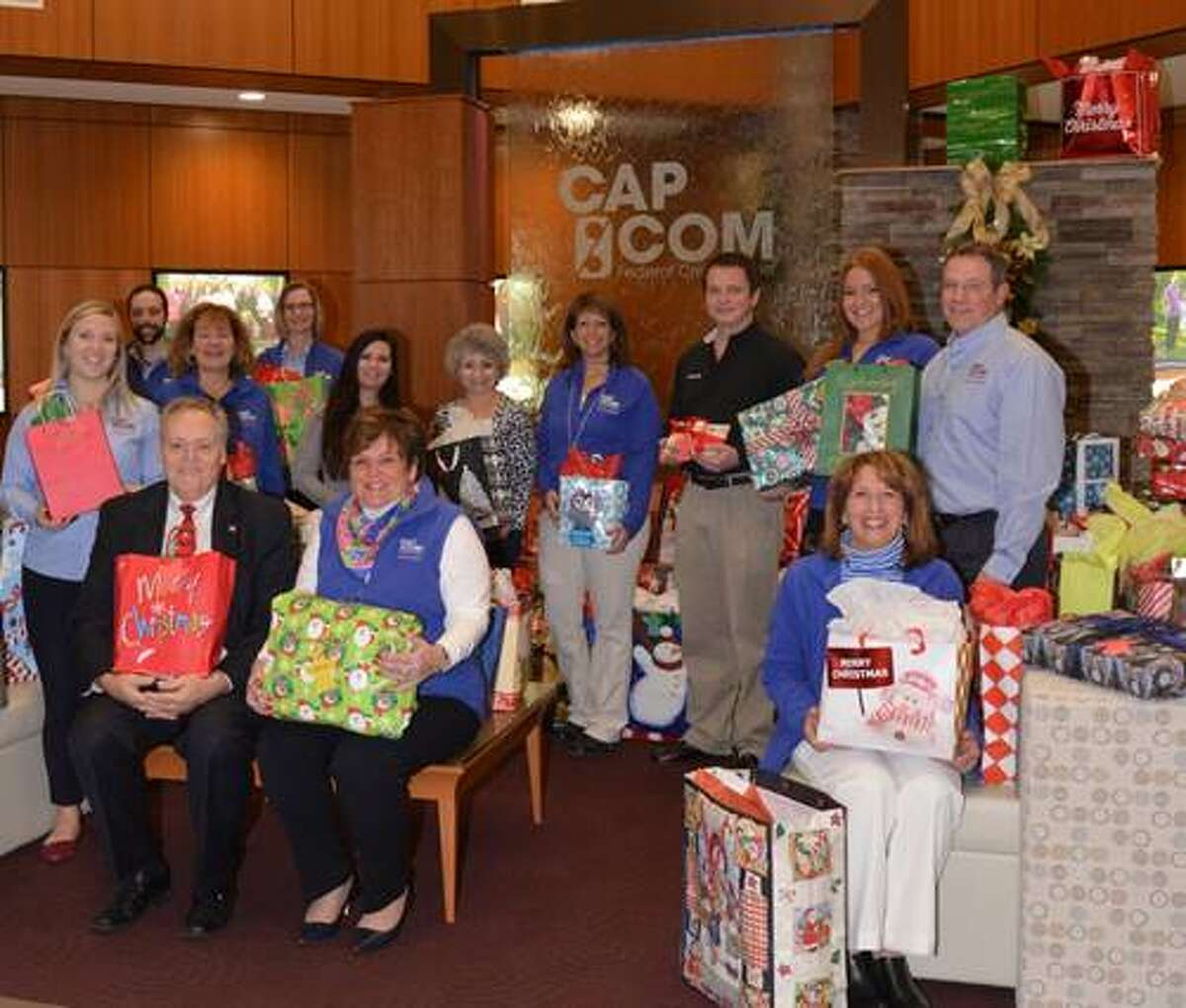 From left, Edward Neary, executive director of Colonie Senior Service Centers; Paula Stopera, president/CEO of CAP COM Federal Credit Union, and staff from CAPCOM and Colonie Senior Service Centers gather to collect gifts in preparation for delivery to seniors this month. (Amanda Goyer)