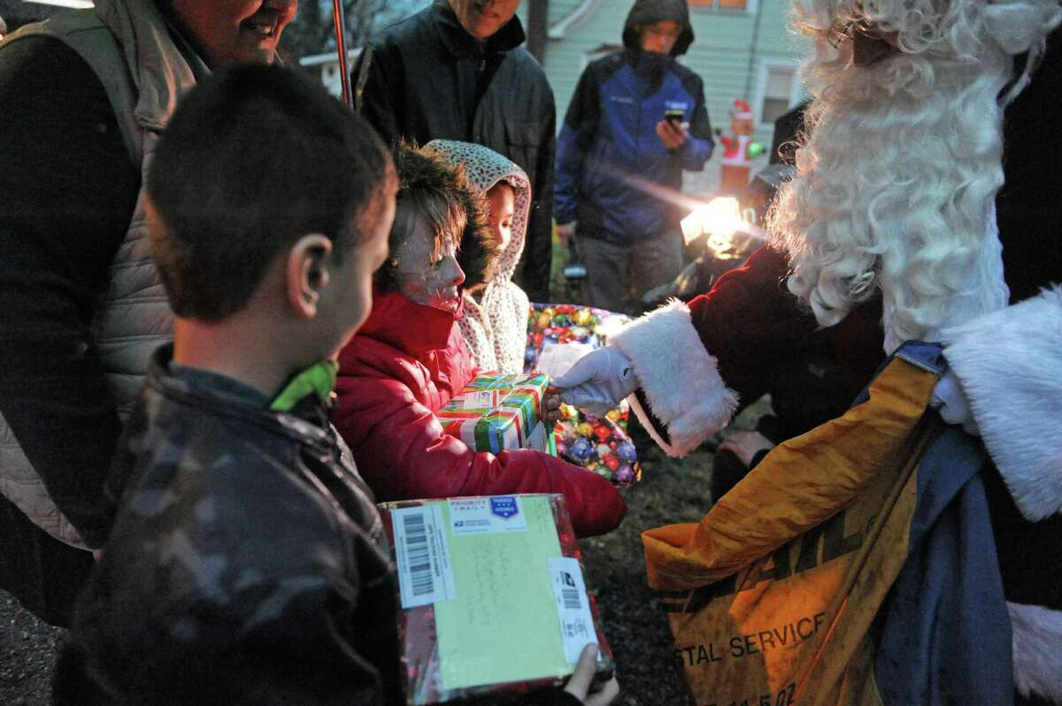 Sa?'Fyre Terry, center, gets gifts from Santa as law enforcement officers and postal workers deliver thousands of cards and packages to her home on Thursday Dec. 17, 2015 in Schenectady, N.Y. (Michael P. Farrell/Times Union)
