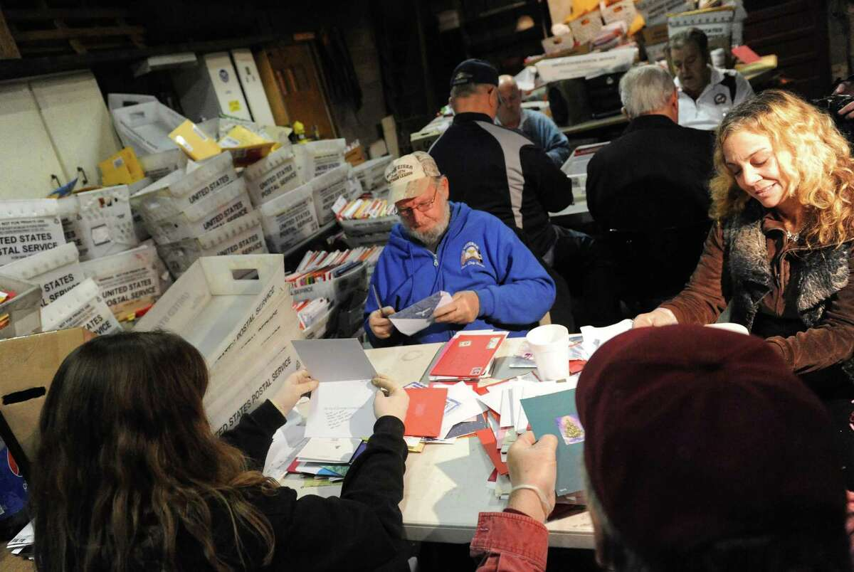 Volunteers open and sort thousands of cards and packages sent to Sa?'Fyre Terry at her home on Thursday Dec. 17, 2015 in Schenectady, N.Y. (Michael P. Farrell/Times Union)