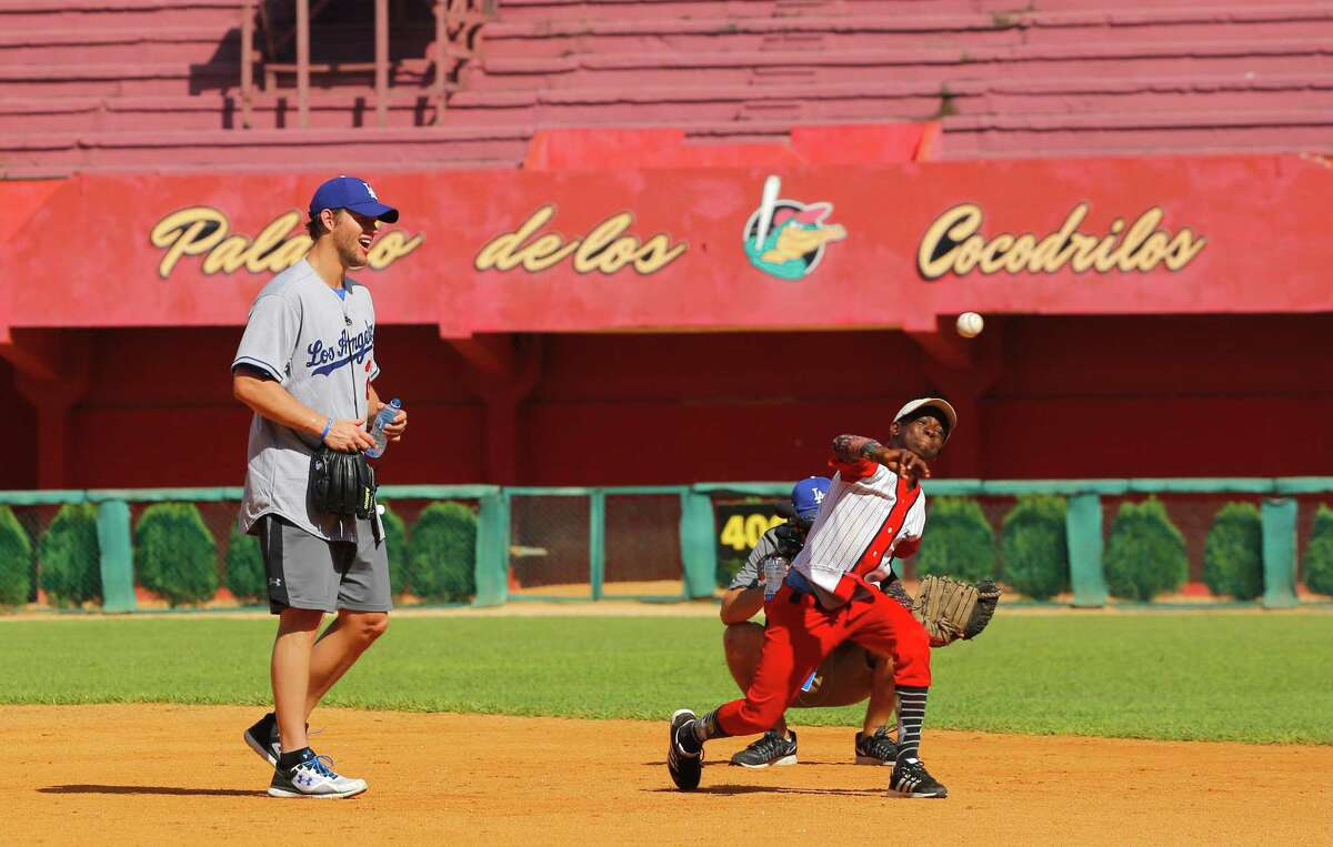Los Angeles Dodgers pitcher Clayton Kershaw, from the U.S., watches a young player throw during a baseball clinic in Matanzas, Cuba, Thursday, Dec. 17, 2015. The clinic is part of a three-day mission meant to warm relations between the U.S. league and this baseball-loving nation. (AP Photo/Desmond Boylan) ORG XMIT: XDB107
