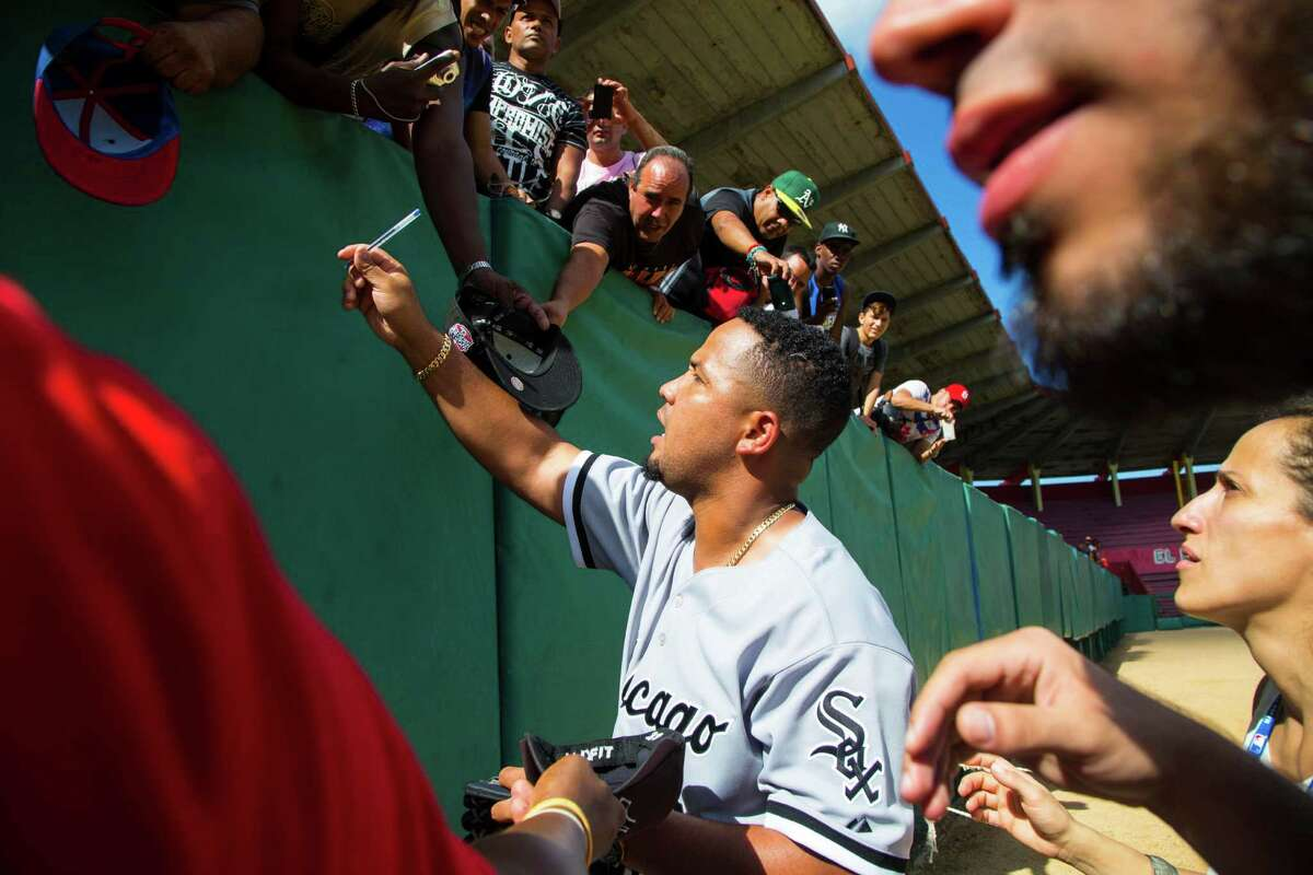 Cuban-born Chicago White Sox first baseman Jose Abreu signs autographs for fans after giving a baseball clinic to young players in Matanzas Cuba, Thursday, Dec. 17, 2015. A lineup of Cuban baseball superstars including some of the most famous defectors in recent memory made a triumphant return to Cuba as part of the first Major League Baseball trip to the island since 1999. (AP Photo/Desmond Boylan) ORG XMIT: XDB111