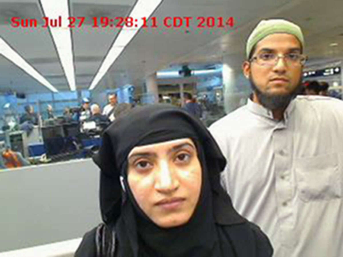 FILE - In this July 27, 2014, file photo, provided by U.S. Customs and Border Protection shows Tashfeen Malik, left, and Syed Farook, as they passed through O'Hare International Airport in Chicago. The bodies of the husband and wife behind the California shootings in San Bernardino on Dec. 2, 2015, have been released by authorities and buried Tuesday, Dec. 15 in Southern California. (U.S. Customs and Border Protection via AP, File) ORG XMIT: NY111