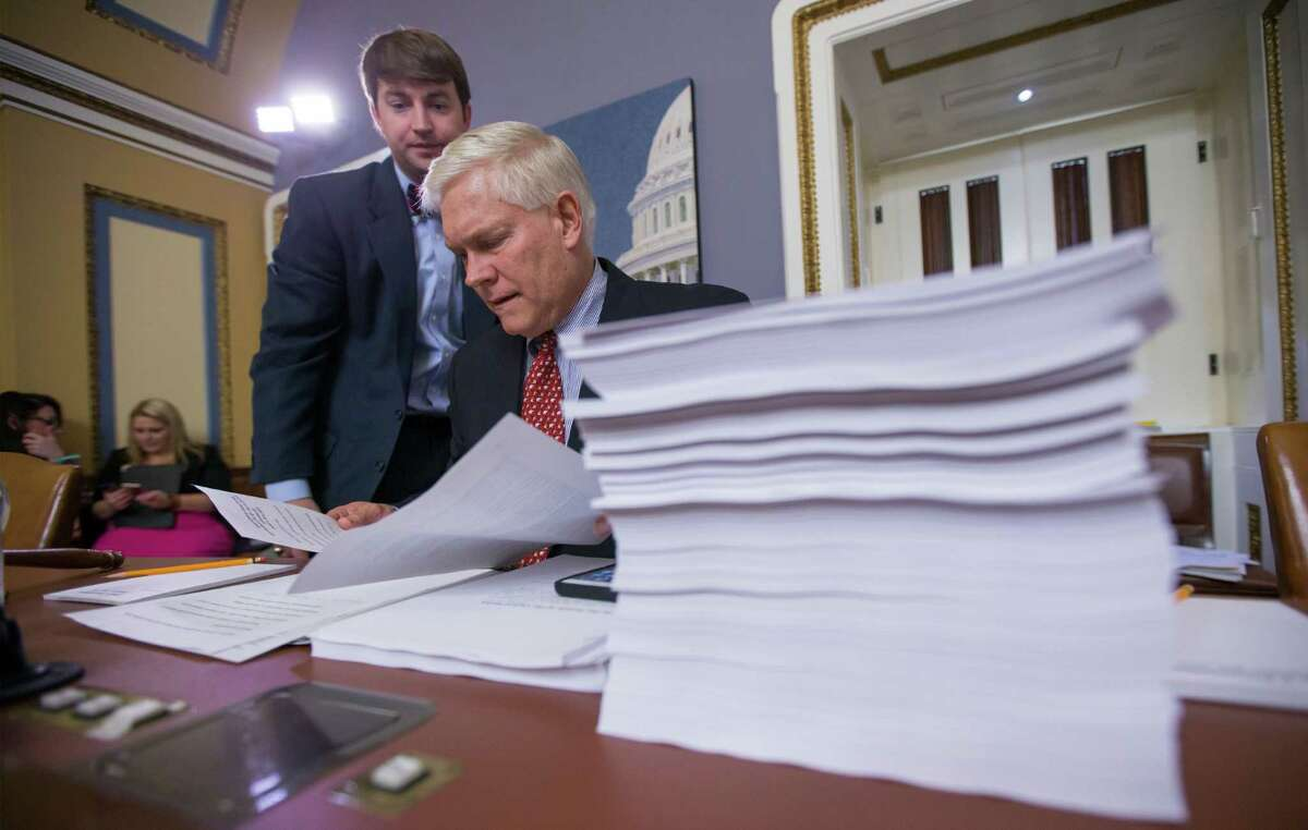 House Rules Committee Chairman Pete Sessions, R-Texas, examines a printout of the $1.1 trillion spending bill to fund the government for the 2016 budget year and extend $680 billion in tax cuts for businesses and individuals, at the Capitol in Washington, Wednesday, Dec. 16, 2015. President Barack Obama is expected to sign the legislation. (AP Photo/J. Scott Applewhite) ORG XMIT: DCSA122