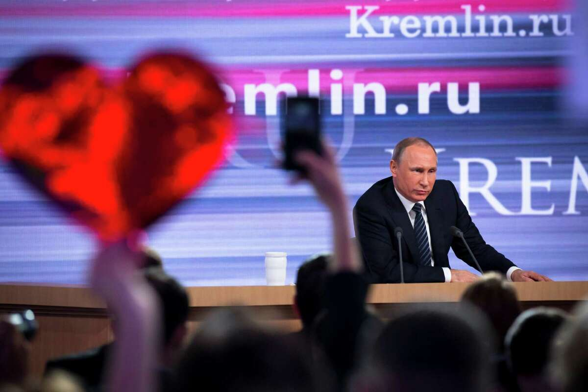 Russian President Vladimir Putin speaks at his annual end of year news conference as a reporter holds up a heart-shaped poster to attract his attention, in Moscow, Russia, Thursday, Dec. 17, 2015. President Vladimir Putin said Thursday Russia is ready to improve ties with the United States and work with whomever is elected its next president. (AP Photo/Alexander Zemlianichenko) ORG XMIT: MOSB106