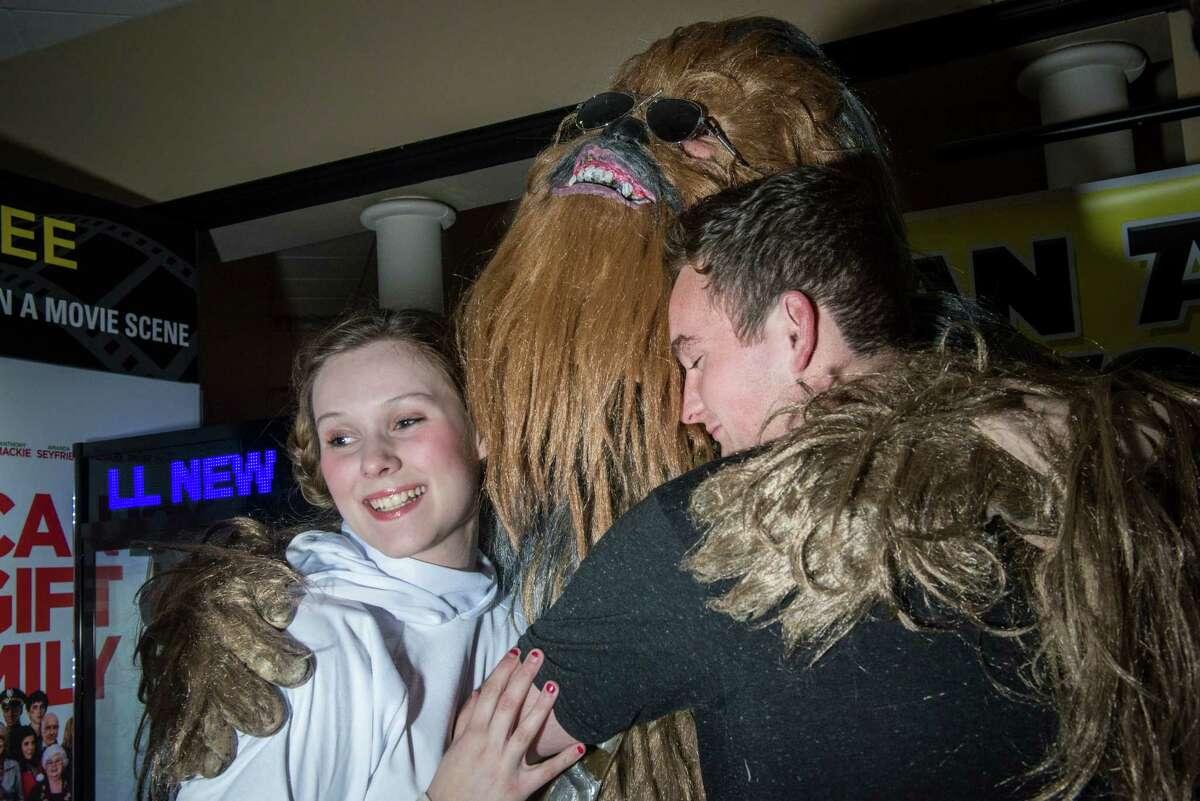 Billy Necessary, dressed as Chewbacca and with the San Antonio Wookiee walk, hugs Josh Hamlin and Heidi Hamlin during the opening of the new Star Wars: The Force Awakens movie at the Santikos Palladium theater in San Antonio, Texas on Thursday, December 17, 2015.