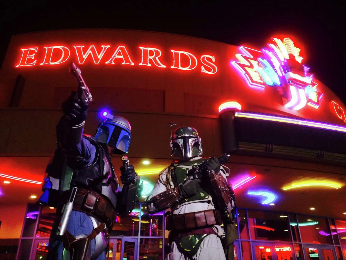 Alex Kammermeier (left), dressed as Jango Fett, and Ryan Krueger (right), dressed as Boba Fett, pose for fans waiting to attend the opening showings of Star Wars Episode VII: The Force Awakens before they attend one themselves at the Edwards Marq-E, Thursday, Dec. 17, 2015, in Houston.