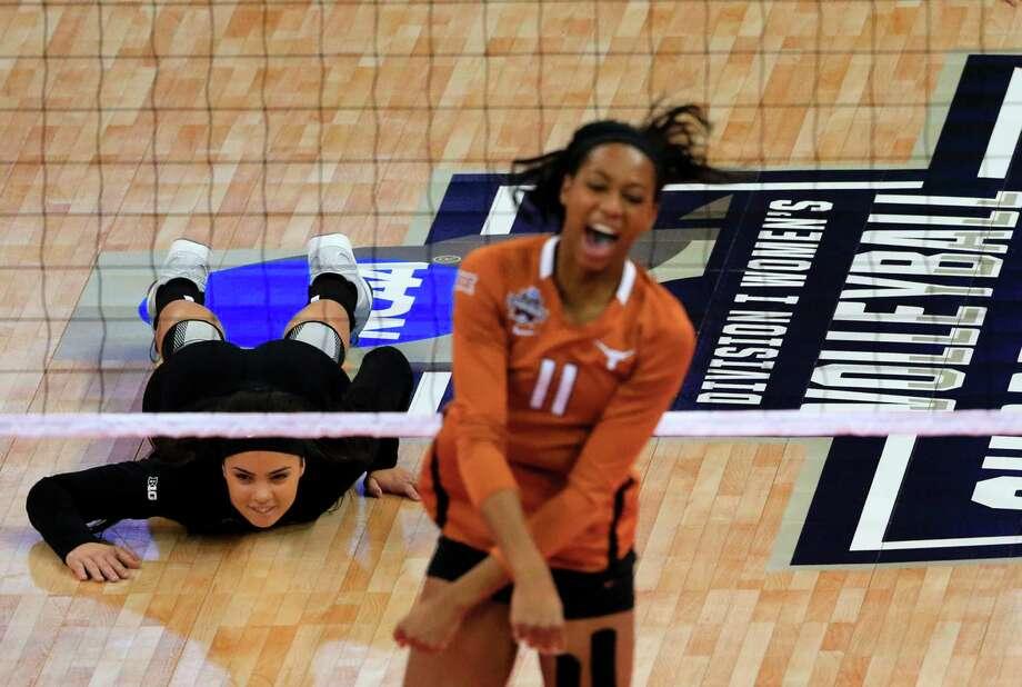 Minnesota's Dalianliz Rosado lies on the court in defeat as Texas' Chiaka Ogbogu celebrates a kill during Thursday night's NCAA women's volleyball semifinal at Omaha, Neb. UT won in four sets. Photo: Nati Harnik, STF / AP