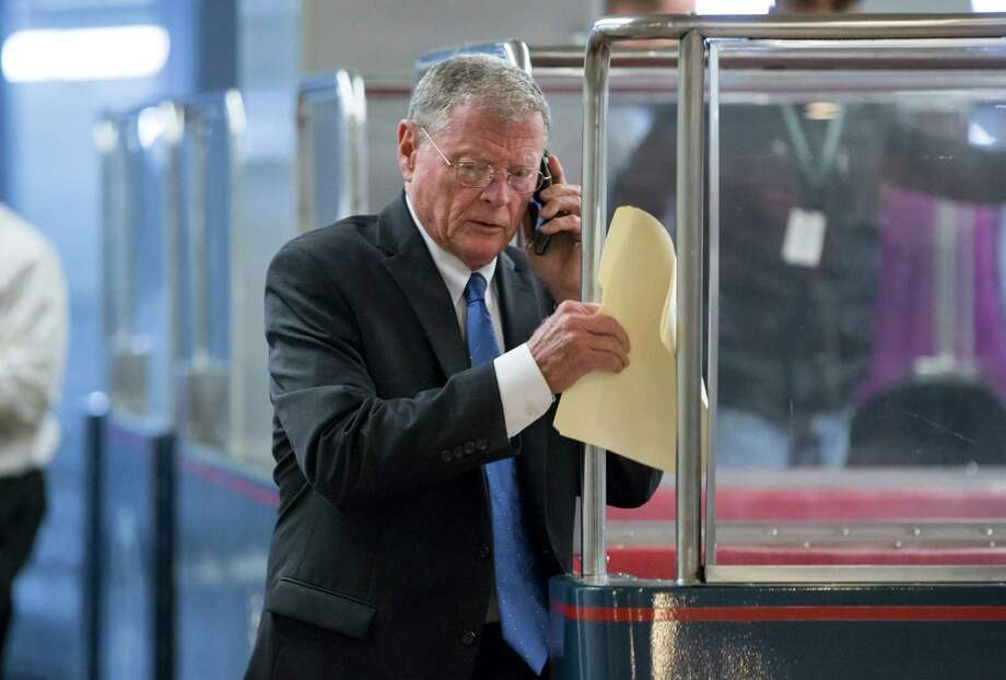 Sen. James Inhofe, R-Okla. talks on the phone as he steps down from a tram on Capitol Hill in Washington, Tuesday, Dec. 15, 2015, as senators gather for weekly party caucuses as White House and congressional negotiators move toward clinching a tax and spending compromise that would cap Congress' year by extending numerous tax credits and financing government agencies in 2016. Differences still remain in the end-of-the-year negotiations and Capitol Hill leaders may need another short stopgap before striking a final agreement. (AP Photo/J. Scott Applewhite) Photo: J. Scott Applewhite, STF / AP