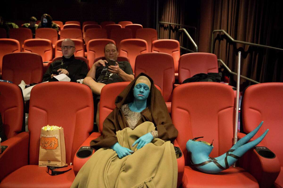 Lisa Merritt, dressed as a Jedi, takes a nap before watching the new Star Wars installment, The Force Awakens, following a 19-hour marathon of the previous films at Cinerama on Thursday, Dec. 17, 2015.