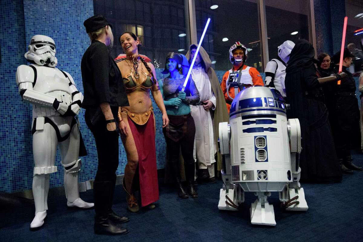 Star Wars cosplayers visit with one another during a break following a 19-hour marathon of the previous Star Wars films before The Force Awakens premiere at Cinerama on Thursday, Dec. 17, 2015.