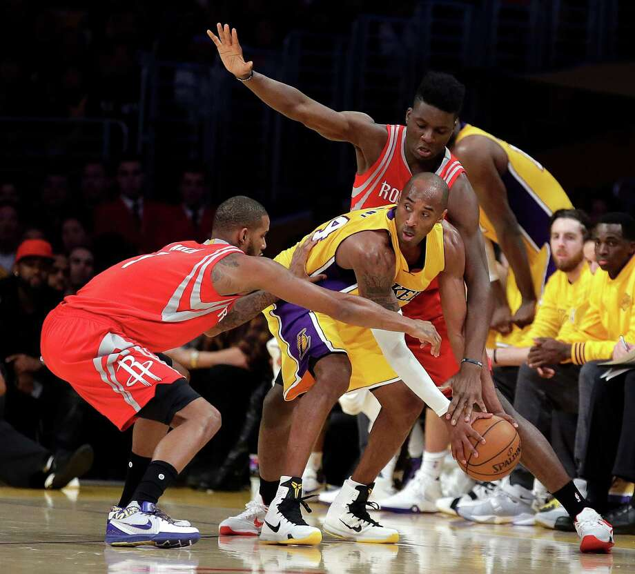 The Lakers' Kobe Bryant feels the squeeze as he becomes the middleman in a Rockets defensive sandwich involving Trevor Ariza, left, and Clint Capela during the first half Thursday night. Photo: Chris Carlson, STF / AP