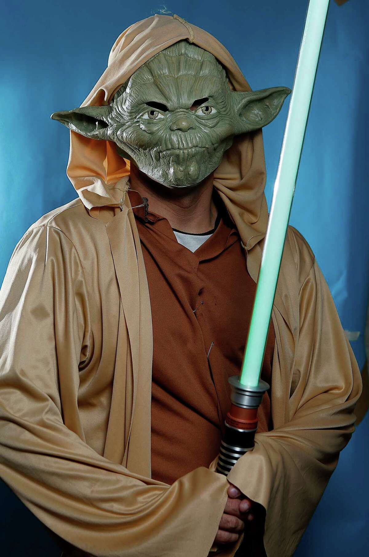 Joshua Ghoreishi dresses as Yoda as he waits to attend the opening showings of Star Wars Episode VII: The Force Awakens at the Edwards Marq-E, Thursday, Dec. 17, 2015, in Houston.