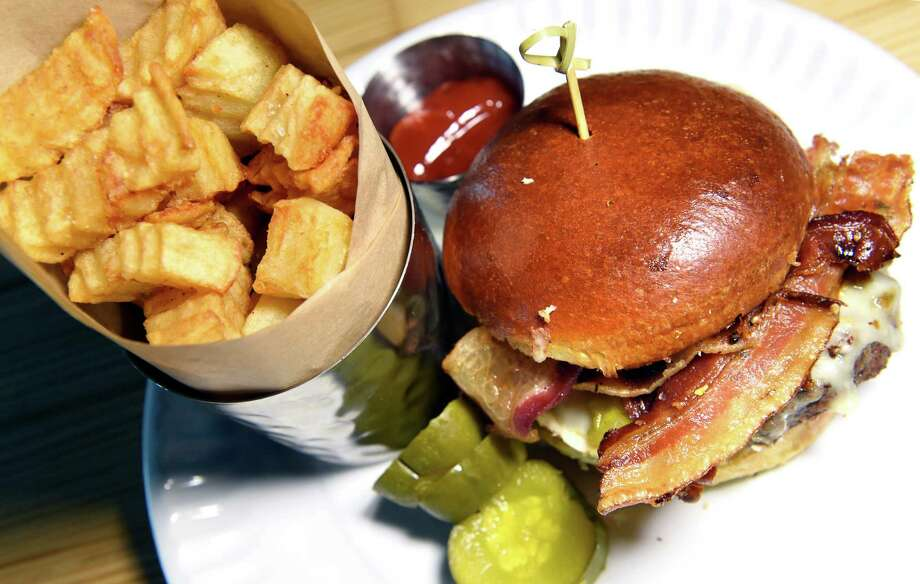 i-Burger features Innovo special grind on a toasted bun with raclette, onion jam, house bacon and served with bread and butter pickles and crinkle cut fries on Thursday, Dec. 10, 2015, at Innovo Kitchen in Latham, N.Y. (Cindy Schultz / Times Union) Photo: Cindy Schultz / 10034605A