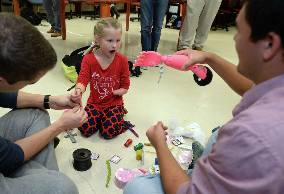 Izzy Miller, 7, expresses excitement Thursday when Seth Ochoa shows her the bracelet he attached to her new 3D printed arm. Several students at Hardin-Jefferson students gave her the arm after creating it using a 3D printer.  Photo taken Thursday, December 17, 2015  Guiseppe Barranco/The Enterprise Photo: Guiseppe Barranco, Photo Editor