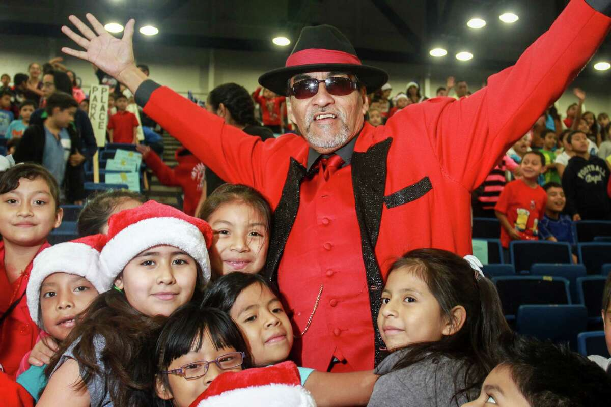 Richard Reyes, or Pancho Claus, is surrounded by students at the Navidad En El Barrio annual Christmas Program at George R. Brown Convention Center. Over 2,000 children from 50 different elementary schools attend the toy giveaway.