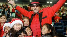 Richard Reyes as Pancho Claus, surrounded by students at the Navidad En El Barrio annual Christmas Program at George R. Brown Convention Center. Over 2,000 children from 50 different elementary schools attend the toy giveaway. (For the Chronicle/Gary Fountain, December 10, 2015)