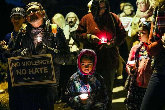 Estrella Burch, 9, (center) held a candle during a multi-faith vigil, where community members discussed Islamophobia and denounced violence, in Berkeley, California on Thursday, December 17, 2015.