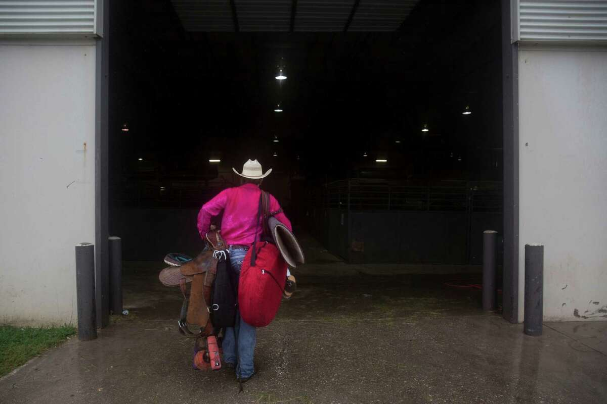Callie duPerier carries her tack and pop-up barrels through the rain before competing in the Women's Professional Rodeo Association World Finals in Waco, Texas on October 23, 2015.