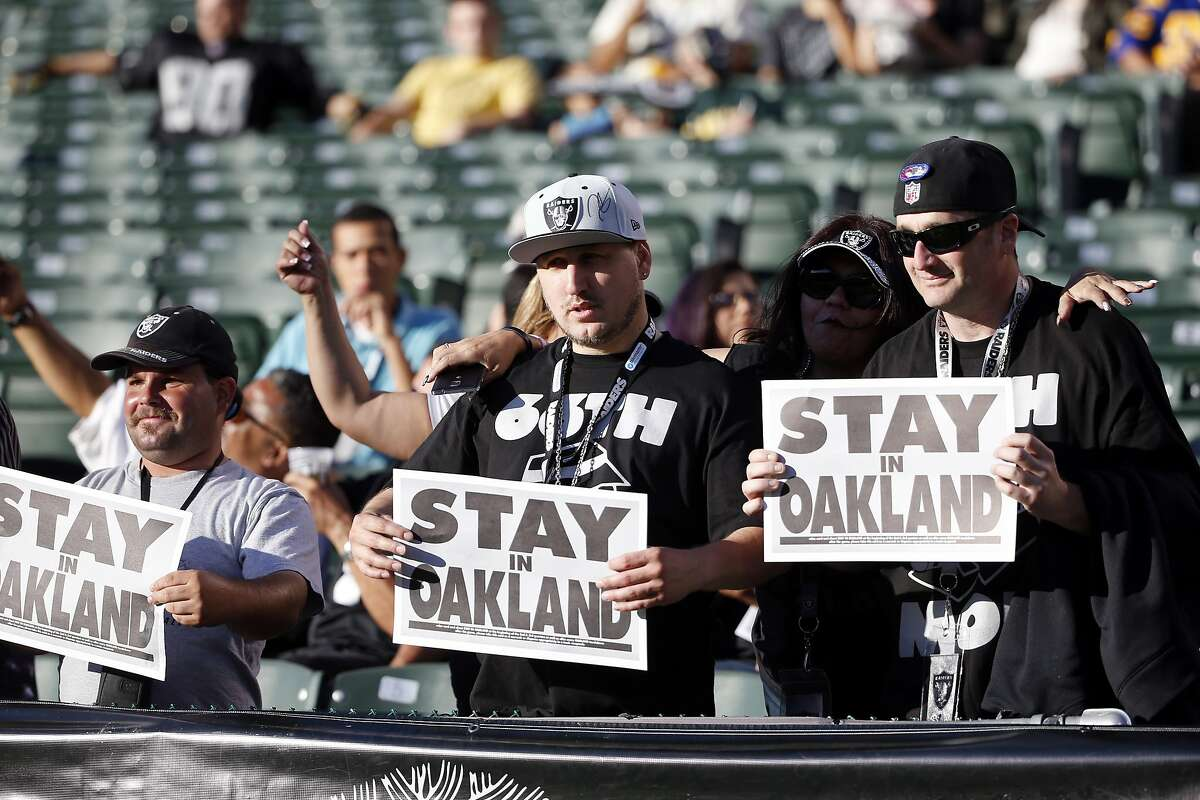 FILE - In this Aug. 14, 2015, file photo, Oakland Raiders fans hold up signs for the team to stay in Oakland before an NFL preseason football game between the Raiders and the St. Louis Rams in Oakland, Calif. The NFL's owners could take a significant step toward the league's return to Los Angeles this week.Or they could decide to take another big step back. Nobody seems certain of the next move in this exhausting dance when the full ownership convenes Wednesday, Dec. 2, 2015, for its annual meetings at a luxury resort outside Dallas. (AP Photo/Tony Avelar, File)