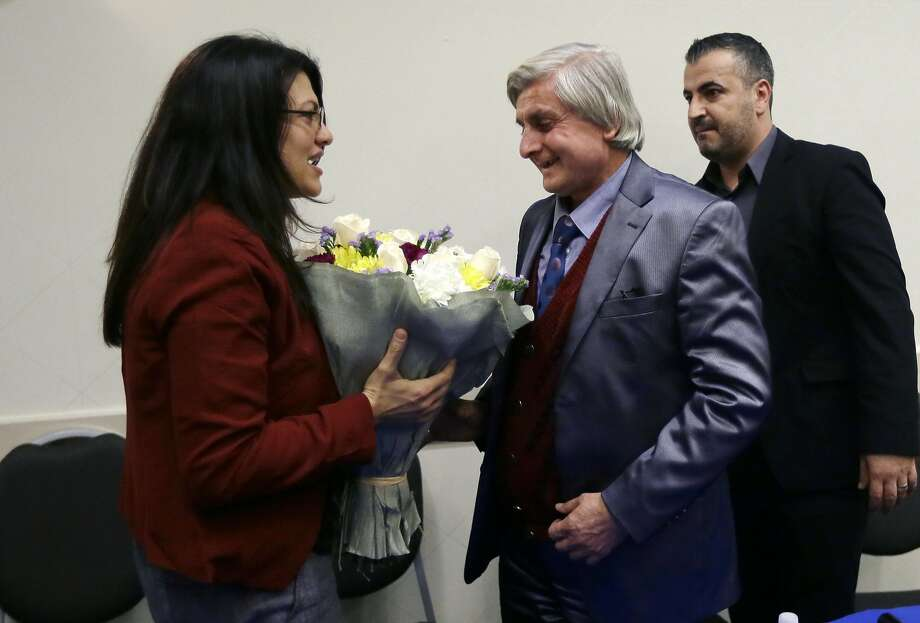 Refaai Hamo (center) is greeted by Michigan state Rep. Rashida Tlaib. A missile attack killed his wife and one daughter. Photo: Carlos Osorio, Associated Press