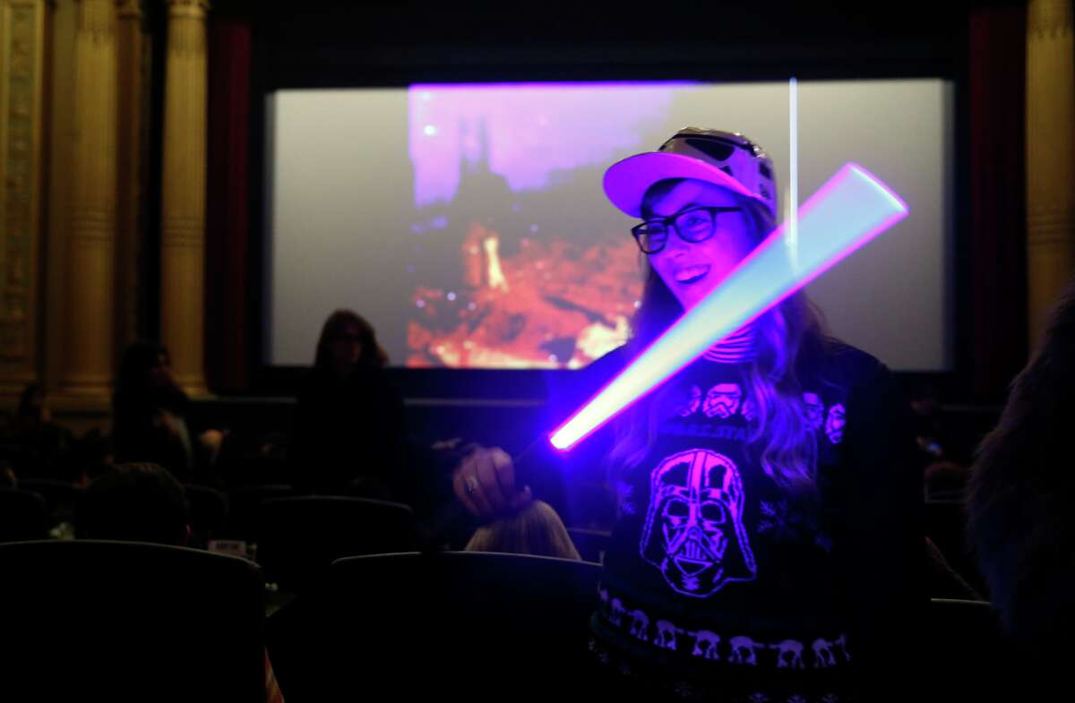 """Acacia Newlon plays with a light saber as she waits for the start of """"Star Wars: The Force Awakens"""" at the Alamo Drafthouse on Mission in San Francisco, on Thursday, December 17, 2015."""