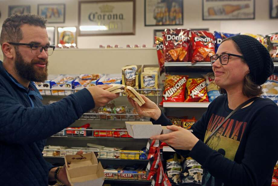 Jeremiah Kosten and Sarah Long raise their sandwiches up in offering a toast — his being of peanut butter and jelly and hers apple butter and jelly, both made by the Bistrobot at Andi's Market in Bernal Heights. Photo: Franchon Smith