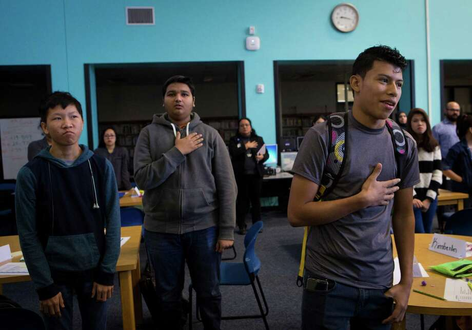 Antony Melendez, right, 16, puts his hand on his heart participating in the pledge allegiance during the second period at Cesar E. Chavez High School along with other newcomers Adhvaryu Bhuvin, center, 17, and Trung Ngo, left, 17, Thursday, Dec. 3, 2015, in Houston. Chavez High School newcomers were gathered at the library for a new student orientation. Photo: Marie D. De Jesus, Houston Chronicle / © 2015 Houston Chronicle