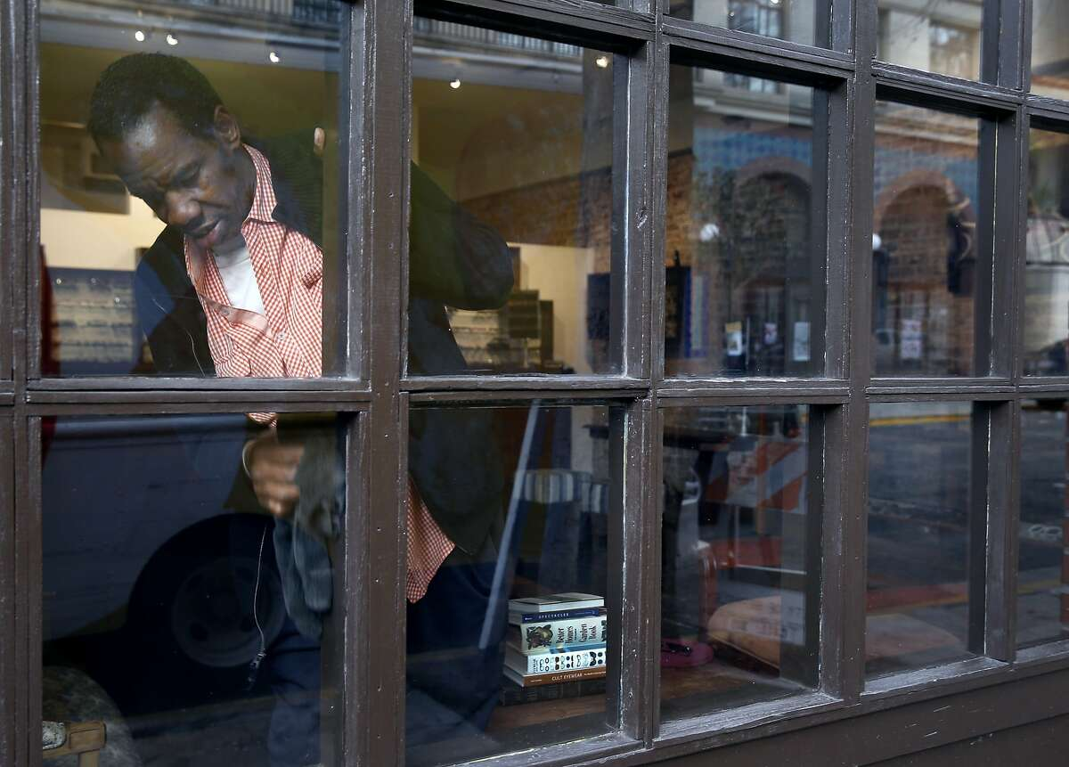 Ronald Bean washes the windows at The Optician eyewear studio in Berkeley, Calif. on Friday, Dec. 18, 2015. Bean suffers from congestive heart failure and makes ends meet by cleaning storefront windows in Berkeley and Oakland. Bean is unable to pay his power bill so he may spend the holidays in the dark.