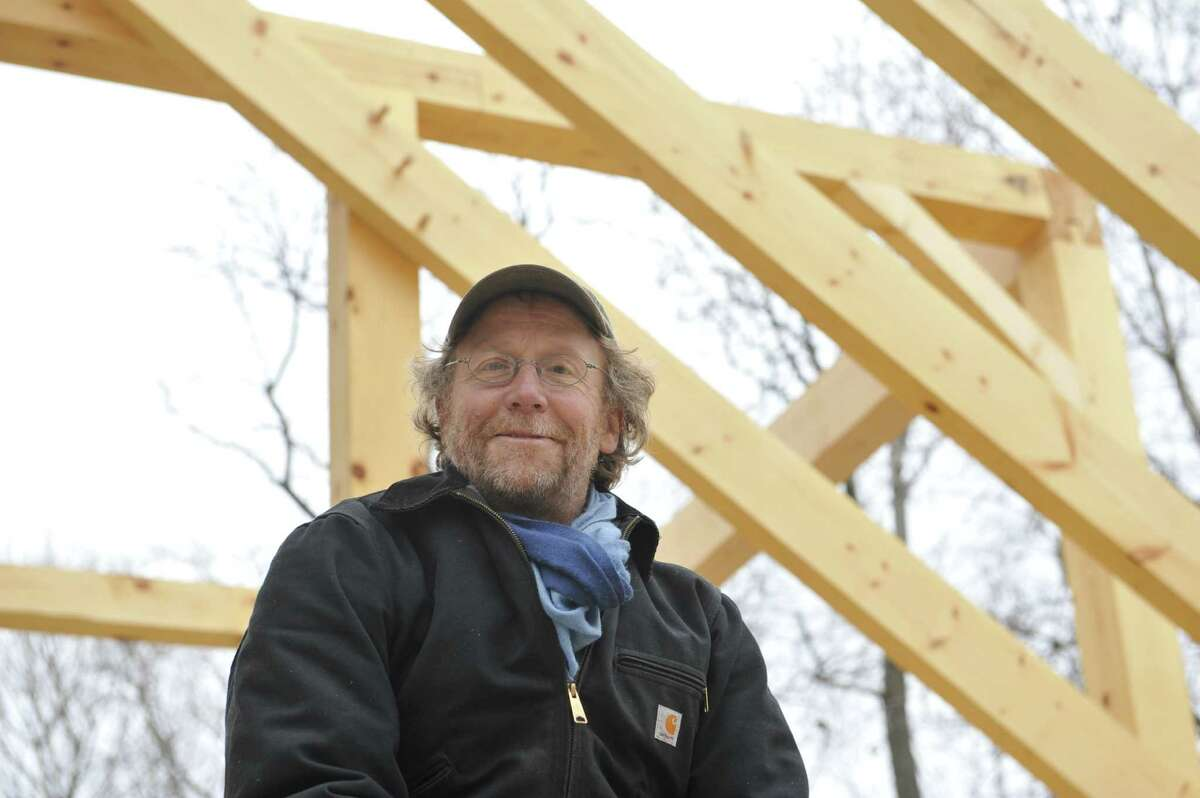Kent Busman poses at his post and beam home being built on Wednesday, Dec. 16, 2015, in Scotia, N.Y. Busman's home is being rebuilt after a fire in January destroyed his home. (Paul Buckowski / Times Union)