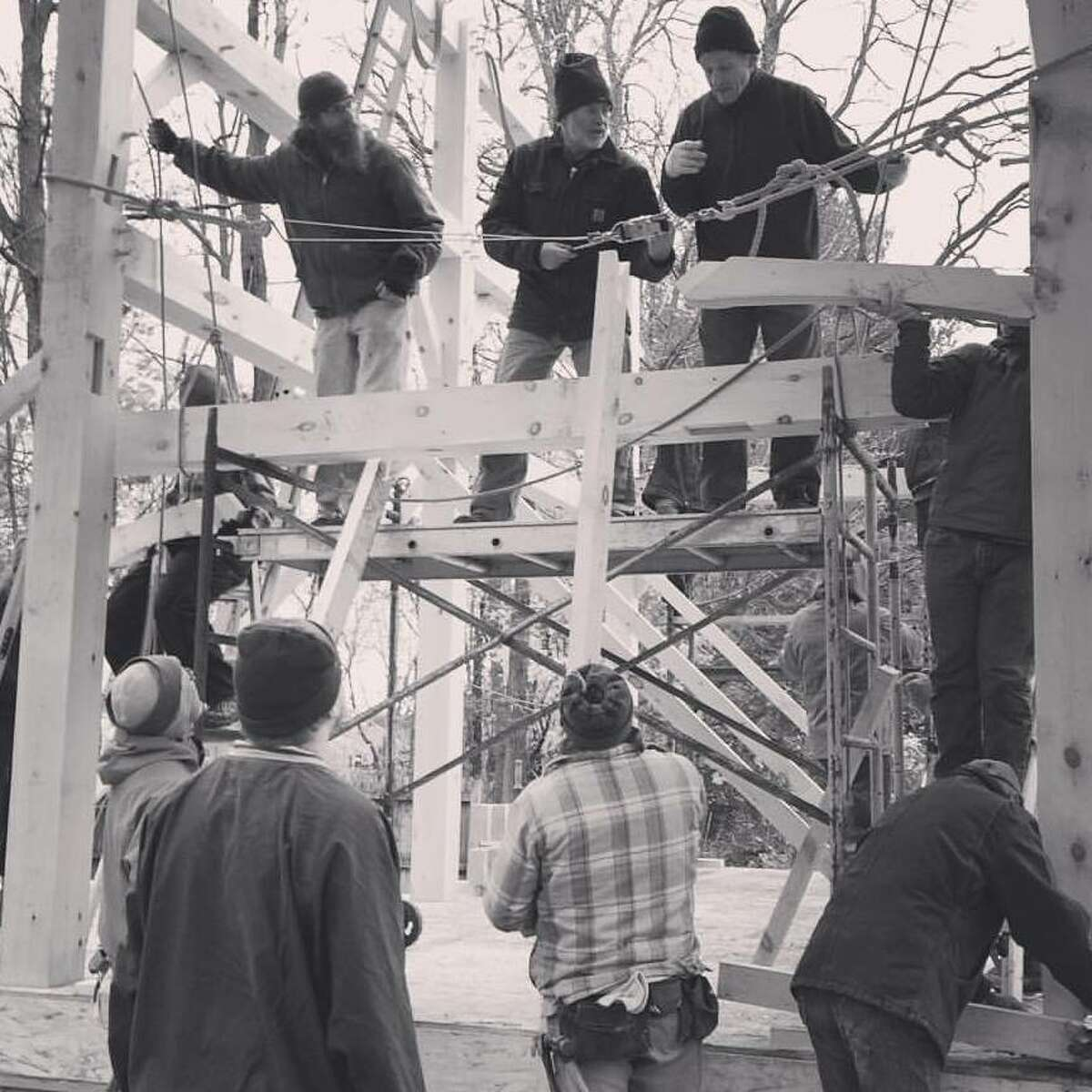 Dan Brudos with volunteers on a scaffolding attaching two bents in the frame of Kent and Jill Busman's post-and-beam home in Scotia on Nov.14, 2015.
