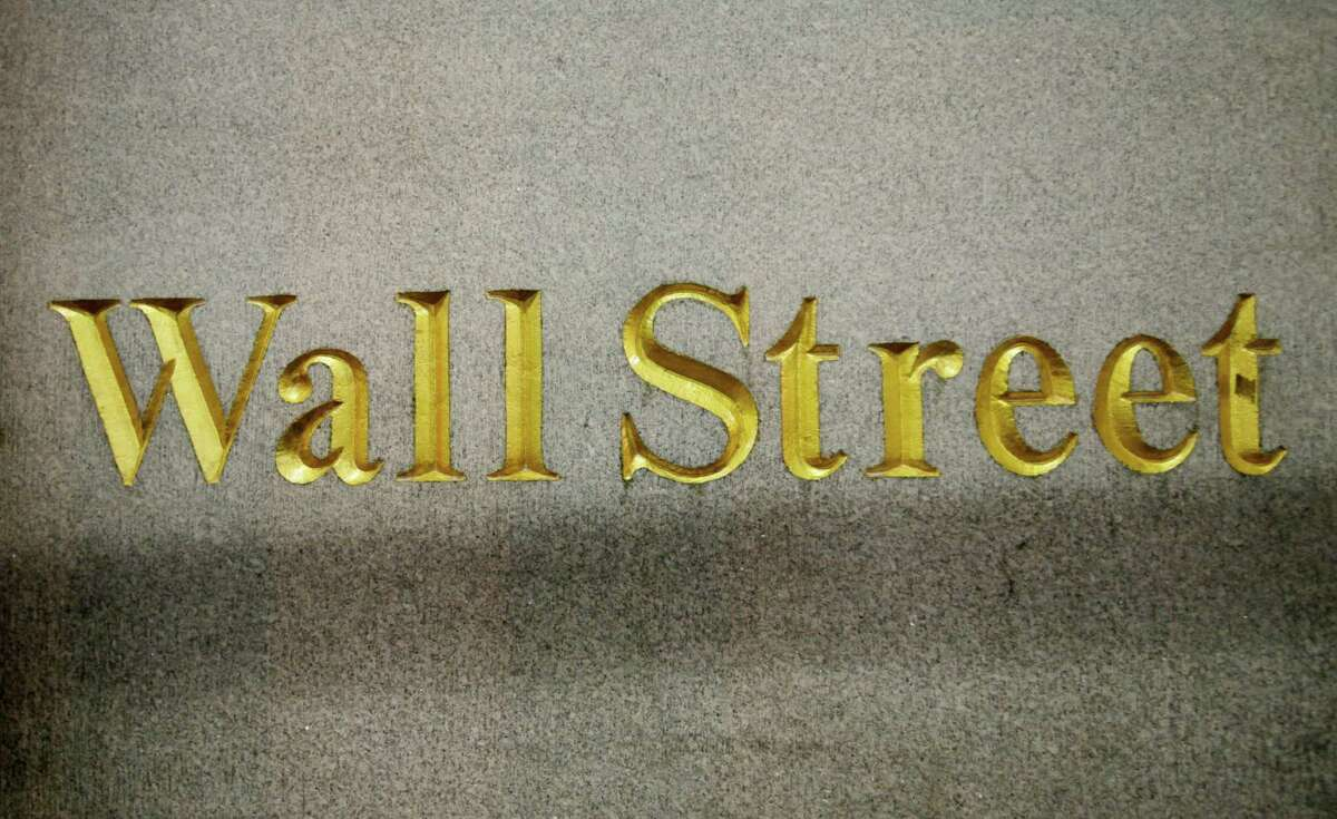FILE - In this Oct. 8, 2014 file photo, a Wall Street address is carved in the side of a building in New York. Global stock markets dropped sharply Friday, Dec. 18, 2015, as a further falls in the the price of oil weighed on investor sentiment, eroding gains sparked the day before by the U.S. Federal Reserve's first rate hike in nearly a decade. (AP Photo/Mark Lennihan, File) ORG XMIT: NY112
