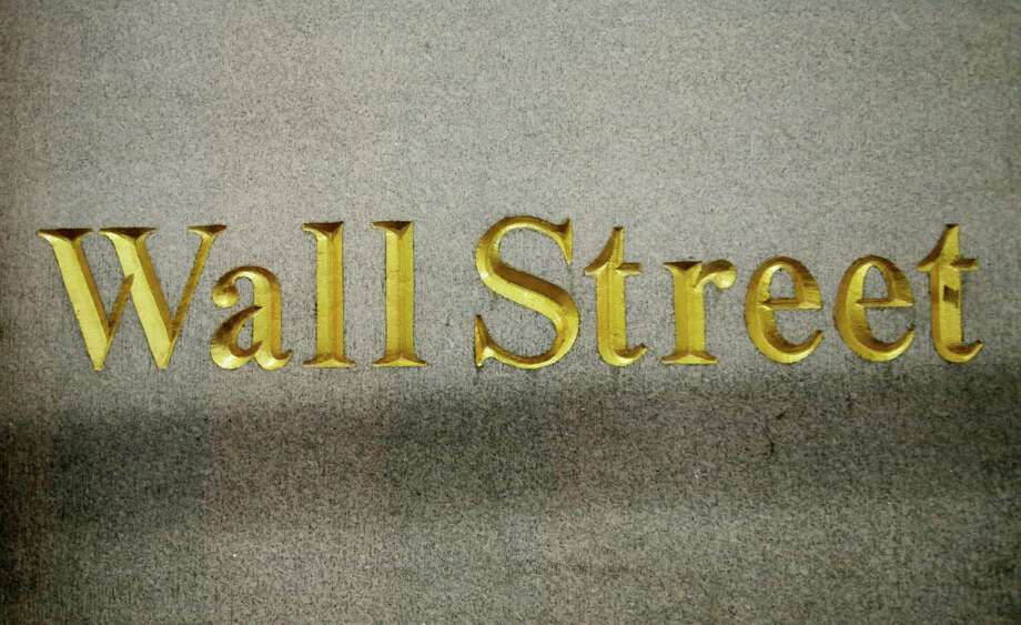 FILE - In this Oct. 8, 2014 file photo, a Wall Street address is carved in the side of a building in New York.  Global stock markets dropped sharply Friday, Dec. 18, 2015,  as a further falls in the the price of oil weighed on investor sentiment, eroding gains sparked the day before by the U.S. Federal Reserve's first rate hike in nearly a decade. (AP Photo/Mark Lennihan, File) ORG XMIT: NY112 Photo: Mark Lennihan / AP