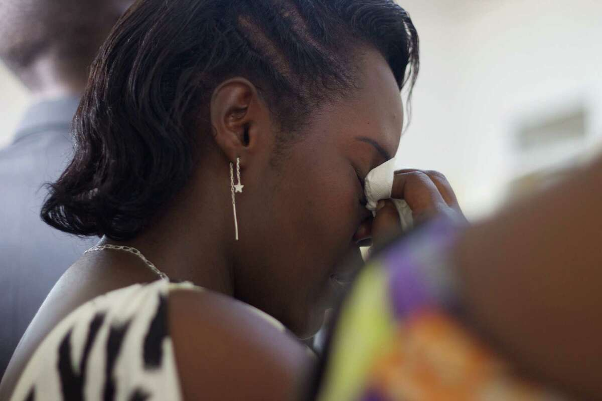 """A young woman wipes tears off her face during the funeral of Egide Niyongere at the Prince Regent Hospital's morgue in Bujumbura, Burundi, Wednesday Dec. 16, 2015. The young man is among the people who were killed during a """"search operation"""" carried out by the Burundian police on Friday, Dec. 11, 2015, following an attack by insurgents on three army camps in the capital. (AP Photo/Melanie Gouby)"""