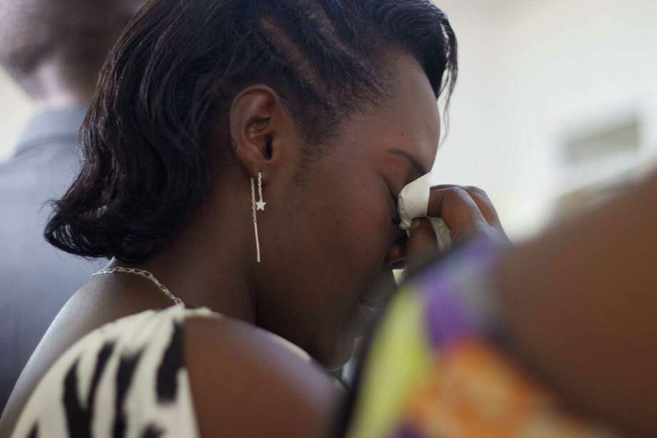 "A young woman wipes tears off her face during the funeral of Egide Niyongere at the Prince Regent Hospital's morgue in Bujumbura, Burundi, Wednesday Dec. 16, 2015. The young man is among the people who were killed during a ""search operation"" carried out by the Burundian police on Friday, Dec. 11, 2015, following an attack by insurgents on three army camps in the capital. (AP Photo/Melanie Gouby) Photo: Melanie Gouby, STR / AP"