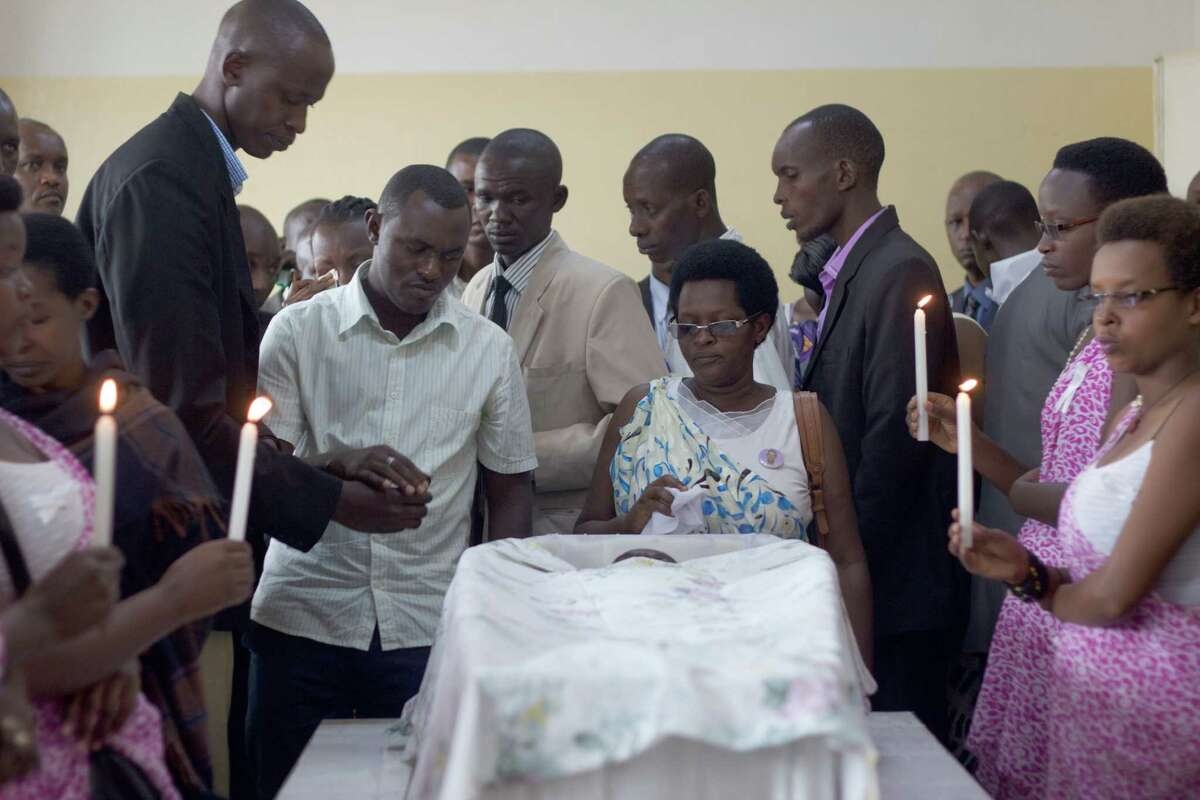"""Friends and relatives gather around Egide Niyongere's coffin for a final goodbye at the Prince Regent Hospital's morgue in Bujumbura, Burundi,Wednesday Dec. 16, 2015. The young man is among the people who were killed during a """"search operation"""" carried out by the Burundian police following an attack by insurgents on three army camps in the capital. (AP Photo/Melanie Gouby)"""