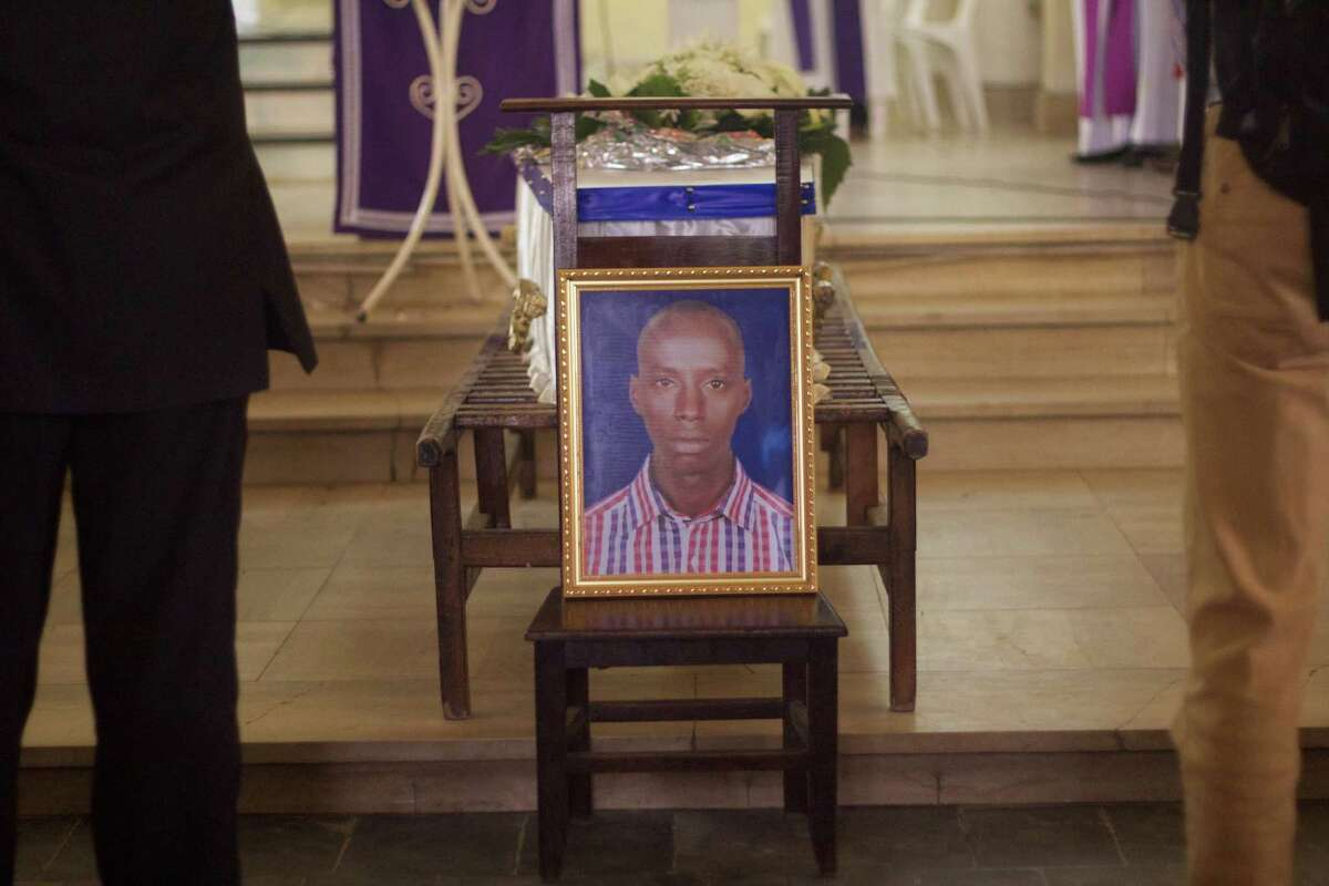 A portrait of Egide Niyongere is displayed in front of his coffin during the mass for his funeral at Bujumbura's cathedral, Burundi, Wednesday Dec. 16, 2015. At least 79 people were killed during counterinsurgency operations carried out by the armband the police following attacks on military camps. Niyongere was among the victims. (AP Photo/Melanie Gouby)
