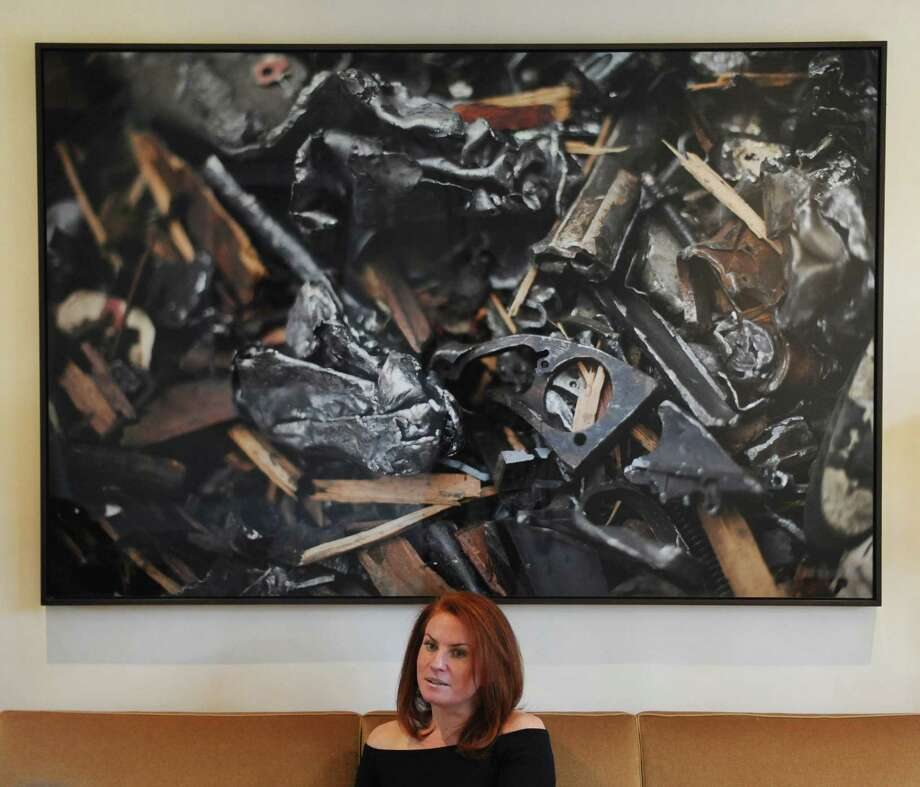 Jessica Mindich, founder and president of the Raise the Caliber jewelry collection, talks about her collection in front of a print by Mark Makela of her company's first gun shred at Sim's Metal Management in Jersey City, N.J., at her home in Greenwich. Raise the Caliber turns guns taken off the street into jewelry and a portion of her line's profits underwrite gun buyback programs in Newark and San Francisco. Photo: Tyler Sizemore / Hearst Connecticut Media / Greenwich Time