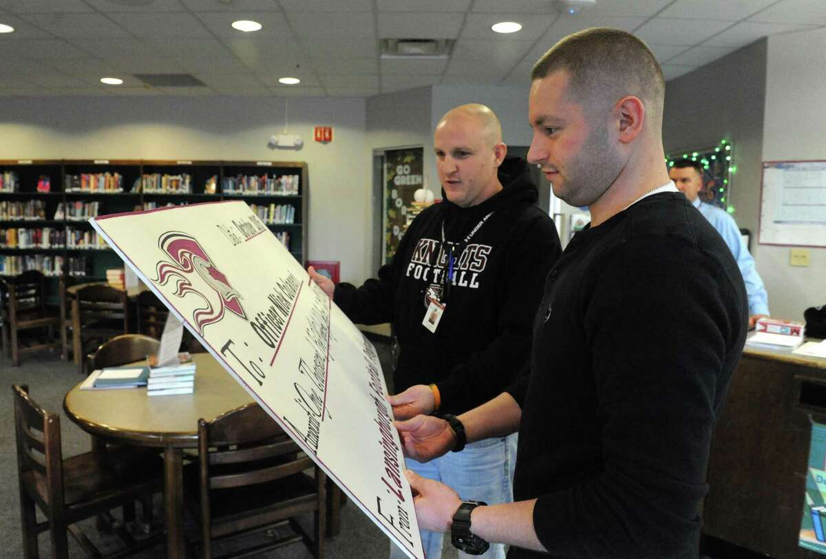 Nick Colaneri, right, a Hoosick Falls officer who has beat cancer but has medical bills, receive a check from Lansingburgh high School football coach Jeff Pasinella on Friday Dec. 18, 2015 in Troy, N.Y. Lansingburgh HS Coaches vs Cancer donated $1,500 to Nick Colaneri. (Michael P. Farrell/Times Union)