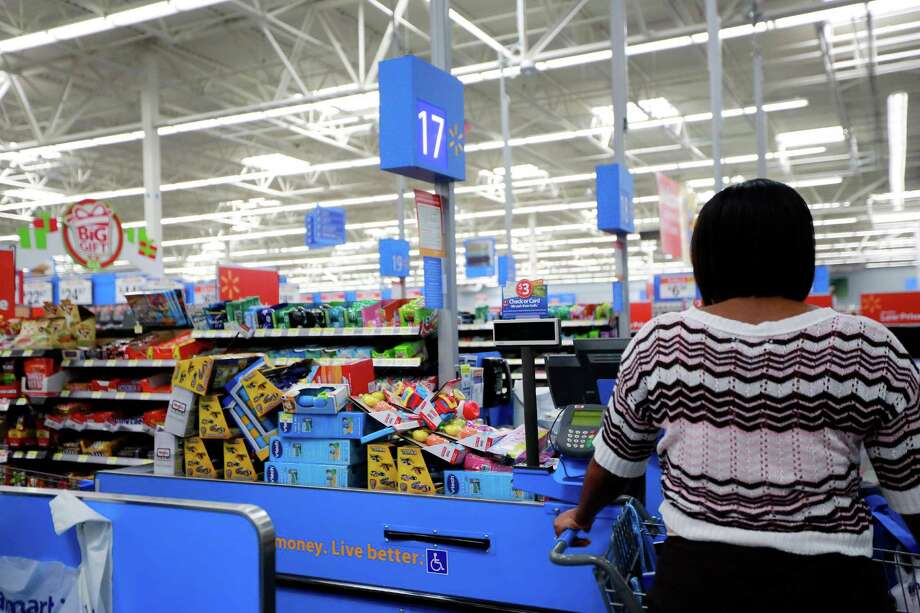 A CPS case worker stands next to a full register for gifts for area foster children, as she prepares to checkout at  Walmart in the Heights neighborhood of Houston on Nov. 19, 2012. (File Photo) Photo: TODD SPOTH, PHOTOGRAPHER / © TODD SPOTH, 2012