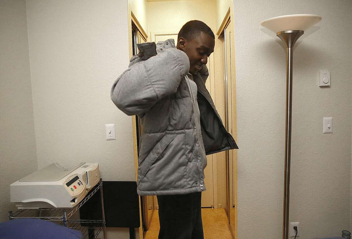 Kelvin Sanders, 20 years old, gets ready to go to his clinic for a check up in Daly City, California, on Friday, December 18, 2015. Behind him is his dialysis machine next to his bed.