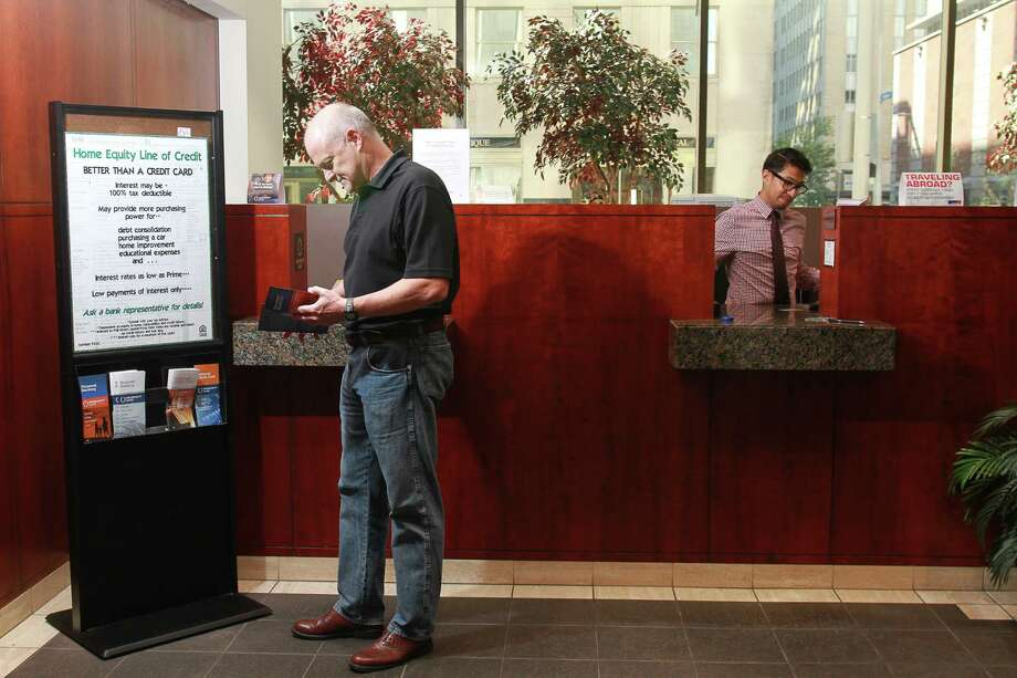 A customer looks at banking brochures while making a deposit at Prosperity Bank's downtown Houston location. (For the Chronicle/Gary Fountain). Photo: Gary Fountain, Freelance / Copyright 2015 by Gary Fountain