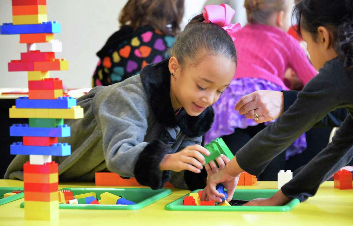 School 14 first grader Mirielys Vasquez-Villeges plays with Lego blocks during a school trip to the exhibit design and fabrication provider Creatacor, Inc., and the LEGO Americana Roadshow Friday Dec. 18, 2015 in Halfmoon, NY. (John Carl D'Annibale / Times Union)