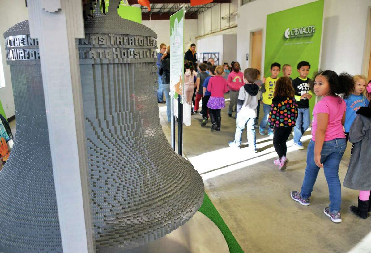 First graders from School 14 in Troy check out a Lego Liberty Bell from the LEGO Americana Roadshow at the exhibit design and fabrication provider Creatacor, Inc., Friday Dec. 18, 2015 in Halfmoon, NY. (John Carl D'Annibale / Times Union)
