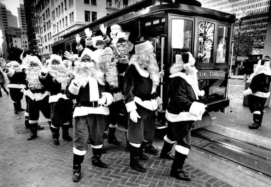 A group of Santas swarm a cable car near the Powell Street turnaround on Nov. 15, 1987. Photo: Frederic Larson / The Chronicle / ONLINE_YES