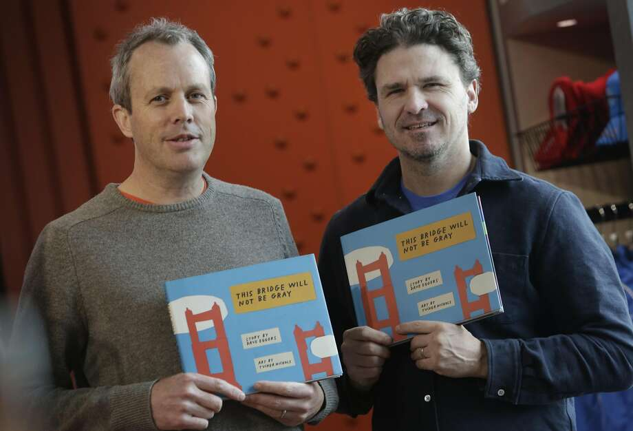 """Dave Eggers (right) and Tucker Nichols (left), hold a copy of their book """"The Bridge Will Not Be Gray"""" at the Golden Gate Bridge Welcome Center on Friday, December 18, 2015 in San Francisco, Calif.  Eggers is the author and Nichols is the illustrator of the book """"This Bridge Will Not Be Gray"""". Photo: Lea Suzuki, The Chronicle"""