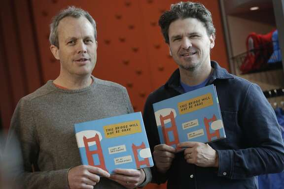 "Dave Eggers (right) and Tucker Nichols (left), hold a copy of their book ""The Bridge Will Not Be Gray"" at the Golden Gate Bridge Welcome Center on Friday, December 18, 2015 in San Francisco, Calif.  Eggers is the author and Nichols is the illustrator of the book ""This Bridge Will Not Be Gray""."