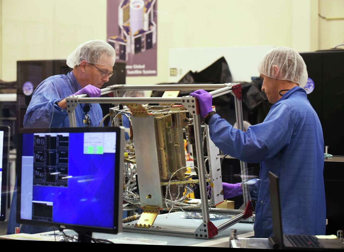 James Foster, left, and Nicholas Alexander help assemble a satellite that will be part of the CYGNSS system, which will use eight satellites to measure from space surface wind speed in hurricanes. The satellite system is being developed and assembled at Southwest Research Institute.