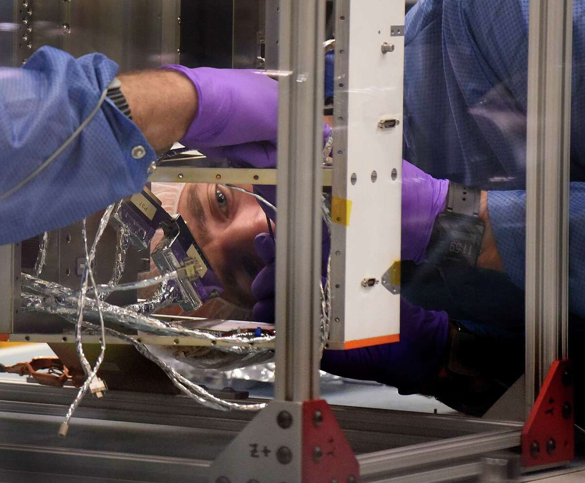 Nicholas Alexander helps assemble a satellite that will be part of the CYGNSS system, which will use eight satellites to measure from space surface wind speed in hurricanes. The satellite system is the first spacecraft fully built at the Southwest Research Institute.